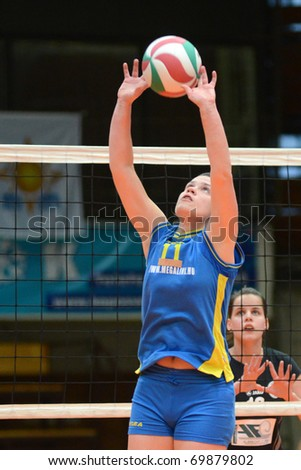 KAPOSVAR, HUNGARY - JANUARY 23: Marianna Palfy (11) posts the ball at the Hungarian NB I. League woman volleyball game Kaposvar vs Miskolc, January 23, 2011 in Kaposvar, Hungary.