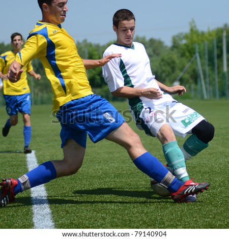 KAPOSVAR, HUNGARY - JUNE 11: Balazs Szili (in white) in action at the Hungarian National Championship under 13 game between Kaposvari Rakoczi FC and Bajai LSE June 11, 2011 in Kaposvar, Hungary. - stock photo