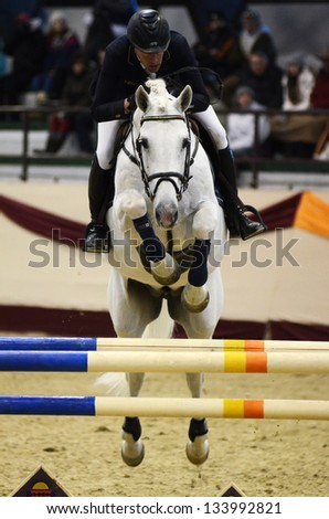 KAPOSVAR, HUNGARY - MARCH 24: Balazs Horvath jumps with his horse (Frederik) on the Masters Tournament International Jumping Competition, March 24, 2013 in Kaposvar, Hungary - stock photo