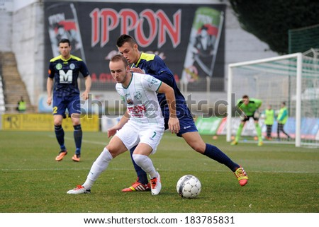 KAPOSVAR, HUNGARY - MARCH 16: Florean Andrei-Alexandru  (white) in action at a Hungarian Championship soccer game - Kaposvar (white) vs Puskas Akademia (blue) on March 16, 2014 in Kaposvar, Hungary. - stock photo