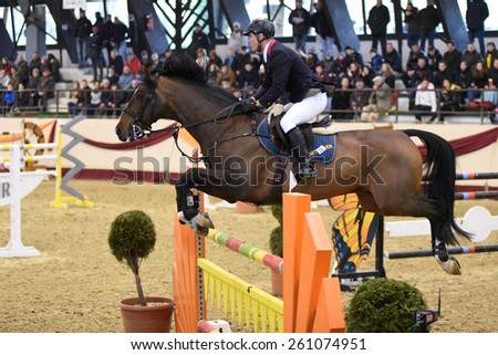 KAPOSVAR, HUNGARY - MARCH 15: Krisztian Buza jumps with his horse (PM Fortuna) on the Masters Tournament International Jumping Competition, March 15, 2015 in Kaposvar, Hungary - stock photo