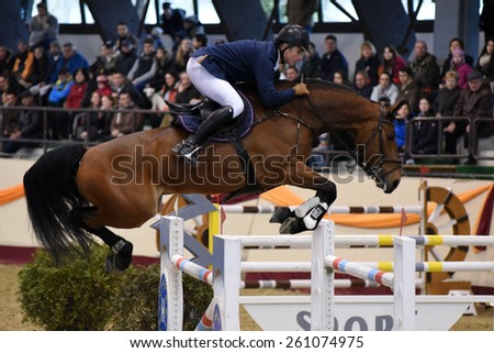 KAPOSVAR, HUNGARY - MARCH 15: Marton Reischl jumps with his horse (Latino) on the Masters Tournament International Jumping Competition, March 15, 2015 in Kaposvar, Hungary - stock photo