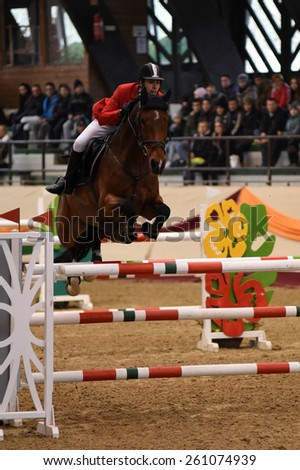 KAPOSVAR, HUNGARY - MARCH 15: Tamas Mraz jumps with his horse (Basco) on the Masters Tournament International Jumping Competition, March 15, 2015 in Kaposvar, Hungary - stock photo