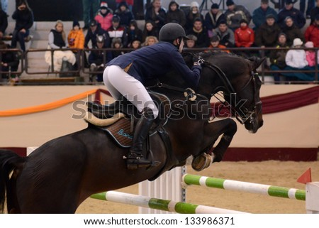 KAPOSVAR, HUNGARY - MARCH 24: Unidentified competitor jumps with his horse on the Masters Tournament International Jumping Competition, March 24, 2013 in Kaposvar, Hungary - stock photo