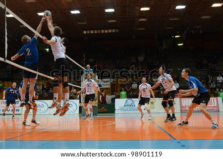 KAPOSVAR, HUNGARY - MARCH 16: Unidentified players in action at a Hungarian Championship volleyball game Kaposvar (white) vs. Kazincbarcika (blue), March 16, 2012 in Kaposvar, Hungary. - stock photo