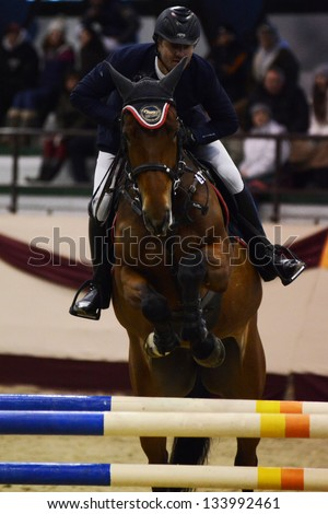KAPOSVAR, HUNGARY - MARCH 24: Vida Vojtec jumps with his horse (Polinetta) on the Masters Tournament International Jumping Competition, March 24, 2013 in Kaposvar, Hungary - stock photo
