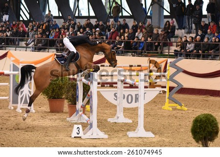KAPOSVAR, HUNGARY - MARCH 15: Zoltan Lazar jumps with his horse (Lacrima Di Felicita) on the Masters Tournament International Jumping Competition, March 15, 2015 in Kaposvar, Hungary - stock photo
