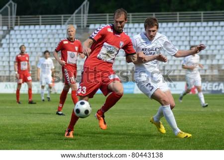 KAPOSVAR, HUNGARY - MAY 14: Milan Peric (in white) in action at a Hungarian National Championship soccer game - Kaposvar vs Szolnok on May 14, 2011 in Kaposvar, Hungary. - stock photo