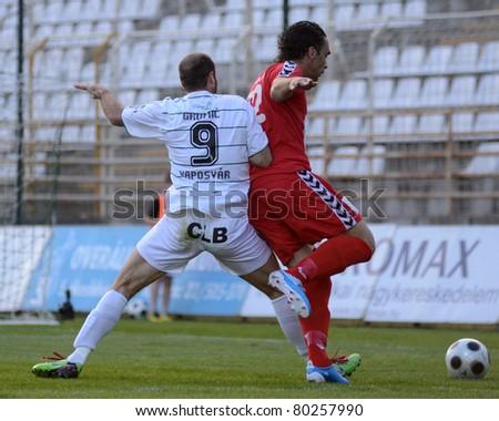 KAPOSVAR, HUNGARY - MAY 14: Miroslav Grumic (in white) in action at a Hungarian National Championship soccer game - Kaposvar vs Szolnok on May 14, 2011 in Kaposvar, Hungary. - stock photo