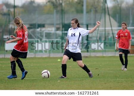 KAPOSVAR, HUNGARY - NOVEMBER 3: Klaudia Csiga (white 14) in action at Hungarian Championship under 15 women soccer game Rakoczi FC (white) vs Pecsi MFC (red) November 3, 2013 in Kaposvar, Hungary. - stock photo