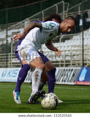 KAPOSVAR, HUNGARY - SEPTEMBER 14: David Hegedus (in white) in action at a Hungarian Championship soccer game - Kaposvar (white) vs Ujpest (purple) on September 14, 2012 in Kaposvar, Hungary. - stock photo