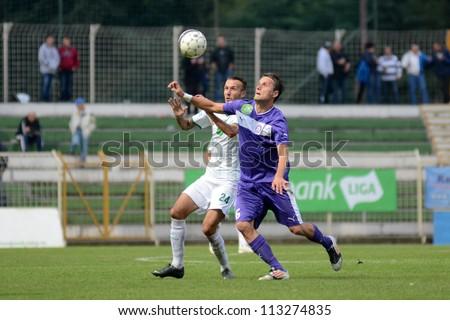 KAPOSVAR, HUNGARY - SEPTEMBER 14: David Hegedus (white 24) in action at a Hungarian National Championship soccer game - Kaposvar (white) vs Ujpest (purple) on September 14, 2012 in Kaposvar, Hungary. - stock photo