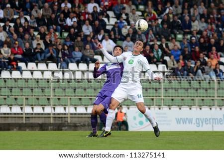 KAPOSVAR, HUNGARY - SEPTEMBER 14: Lorant Olah (in white) in action at a Hungarian National Championship soccer game - Kaposvar (white) vs Ujpest (purple) on September 14, 2012 in Kaposvar, Hungary. - stock photo