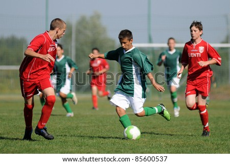 KAPOSVAR, HUNGARY - SEPTEMBER 11: Roland Vajda (green) in action at the Hungarian National Championship under 15 game between Kaposvar (green)  and Lenti (red) September 11, 2011 in Kaposvar, Hungary. - stock photo