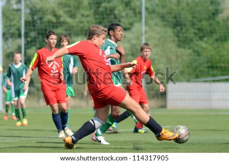 KAPOSVAR, HUNGARY - SEPTEMBER 22: Unidentified players in action at the Hungarian Championship under 15 game between Rakoczi (green) and Mezga FC (red) September 22, 2012 in Kaposvar, Hungary. - stock photo
