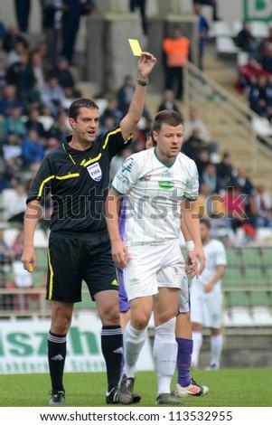 KAPOSVAR, HUNGARY - SEPTEMBER 14: Viktor Kassai (referee) in action at a Hungarian Championship soccer game - Kaposvar (white) vs Ujpest (purple) on September 14, 2012 in Kaposvar, Hungary. - stock photo