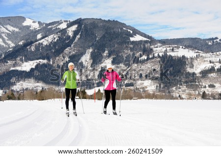 KAPRUN, AUSTRIA - FEBRUARY 2, 2015. Two ladies run on skies in cross-country skiing area near Kaprun, Austria.   - stock photo