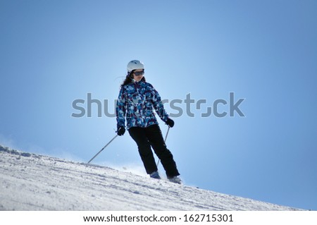 KAPRUN - MARCH 5: Unidentified skier skiing down the slope in a beautiful sunny day, in the Austrian Alps, during the school vacation. On March 5, 2013, in Kitzsteinhorn, Austria