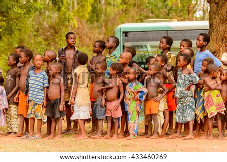 KARA, TOGO - MAR 9, 2013: Unidentified Togolese children watch the local music show. Children in Togo suffer of poverty due to the unstable econimic situation