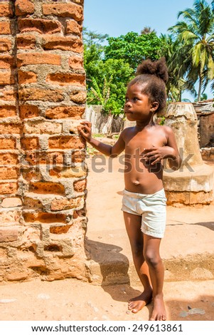 KARA, TOGO - MAR 9, 2013: Unidentified Togolese cute girl stays near a red brick wall. People in Togo suffer of poverty due to the unstable econimic situation