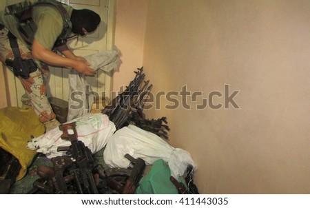 KARACHI, PAKISTAN - APR 26: Rangers commandoes exposing seized ammunition recovered from political activist during raid at Nine Zero, the Secretariat of MQM on April 26, 2016 in Karachi. - stock photo