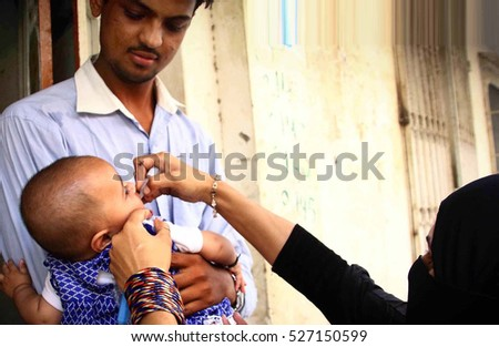 KARACHI, PAKISTAN - DEC 01: Anti- polio worker administrating vaccine to children during campaign in Mehmoodabad area on December 01, 2016 in Karachi.