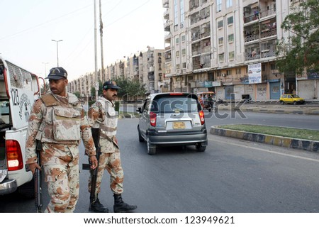 KARACHI, PAKISTAN - JAN 08: Rangers stand alerts to avoid untoward incident  while shops seen closed after clash between two groups at Rabia City in Gulistan-e-Johar on January 08, 2013  in Karachi.