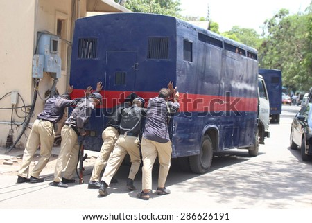 KARACHI, PAKISTAN - JUN 12: Police van included into convoy escorting MQM leader Amir Khan is being  pushing by police staffs showing negligence of concerned authorities on June 12, 2015 in Karachi.
