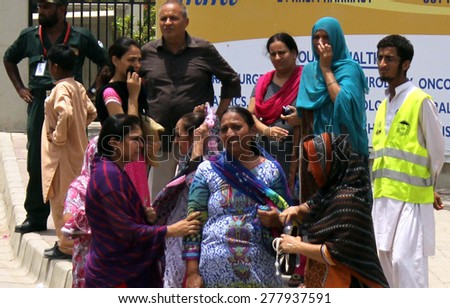 KARACHI, PAKISTAN - MAY 13: Ismaili people mourn the killing of their relatives as the  six unidentified assailants on motorbikes opened fire on a bus 43 dead and 24 injured on May 13, 2015 in Karachi. - stock photo