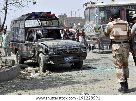 KARACHI, PAKISTAN - MAY 06: Security officials are gathering at venue after bomb attack on police van caused two policemen injured including officer Farooq, at North Karachi area on  May 06, 2014.