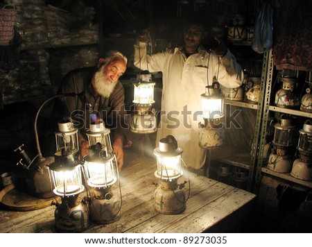 KARACHI, PAKISTAN - NOV 21: A shopkeeper carries lanterns on rent for his shop during electricity load-shedding in a main commercial market of city in Karachi on Monday, November 21, 2011. - stock photo