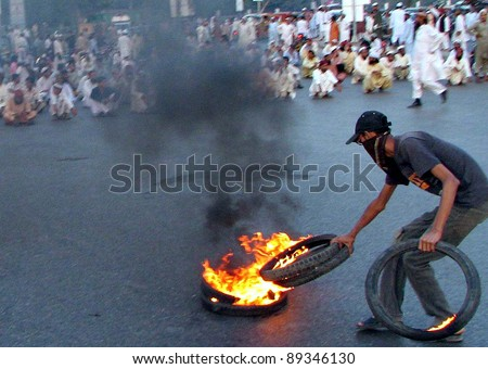 KARACHI, PAKISTAN - NOV 22: An angry protester burns tyres during protest demonstration of Jamat Ahle Sunnat in favor of their demands at MA.Jinnah road on November 22, 2011in Karachi. - stock photo