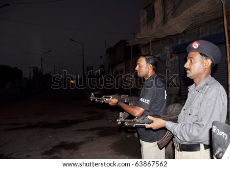 KARACHI, PAKISTAN - OCT 26: Police officials stand guard at street during search operation in Jahanabad area on October 26, 2010 in Karachi.