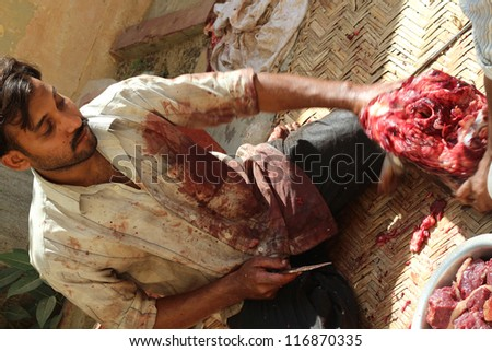 KARACHI, PAKISTAN-OCTOBER 28: Unidentified butcher slaughters a cow on Eid-Al-Adha, the feast of sacrifice, on October 28, 2012 in Karachi, Pakistan. - stock photo