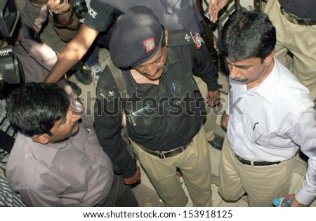 KARACHI, PAKISTAN - SEP 12: Police escort Muttahida Qaumi Movement (MQM)  sector in-charge and former MPA Nadeem Hashmi after case hearing at Anti Terrorism Court on September 12, 2013 in Karachi.
