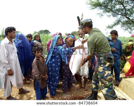 KARACHI, PAKISTAN - SEPT. 15: Navy soldiers distribute ration among flood affected people at a flood hit area of Sindh province in Karachi, Pakistan on September 15, 2011.