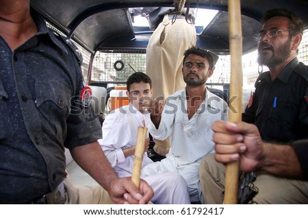 KARACHI,PAKISTAN-SEPT 24:Police officials escort to men after their arrest during protest demonstration of Islami Jamiat Talba to condemn the verdict against Dr.Aafia Siddiqui Sept 24, 1010 in Karachi