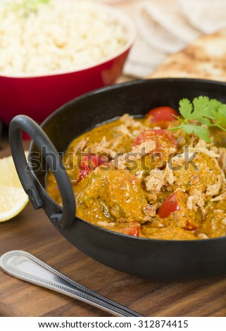 Karahi Gosht - Mutton curry cooked with tomatoes and topped with fried onions. Served with naan bread, pilau rice and poppadoms. - stock photo