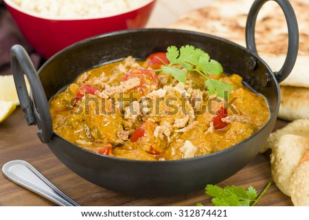 Karahi Gosht - Mutton curry cooked with tomatoes and topped with fried onions. Served with naan bread, pilau rice and poppadoms.