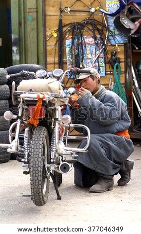 KARAKORUM , MONGOLIA - 30-04-2008; Young Mongolian man with traditional clothing, is preparing a motorbike at his shop at the town Karakorum