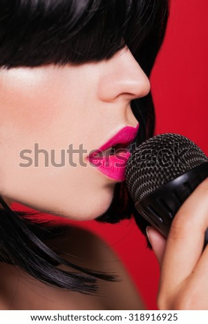 Karaoke. Beautiful young woman model singing with a microphone on red background.  - stock photo