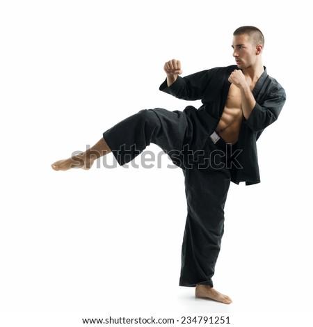Karate black belt delivers high side kick - stock photo