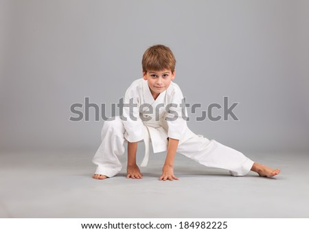 Karate boy in white kimono fighting isolated on gray background