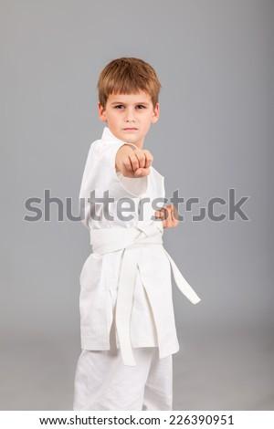 Karate boy in white kimono fighting isolated on gray background - stock photo