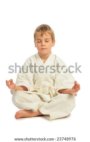 Karate boy meditates - stock photo