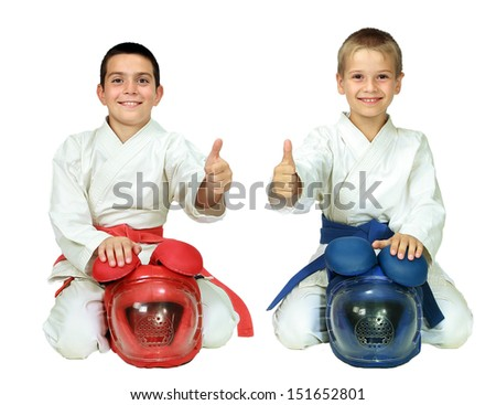 Karate children sit in a ritual pose with helmets and point the finger isolated  - stock photo