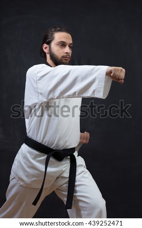 Karate Fighter in white Kimono Isolated on Black with Copy space