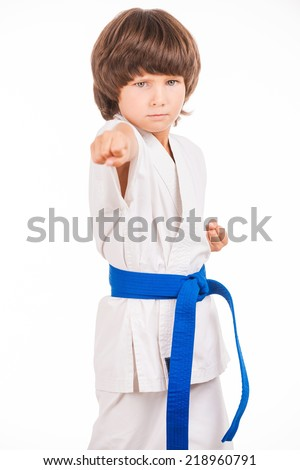 Karate kid. Little boy doing martial arts moves while isolated on white background - stock photo