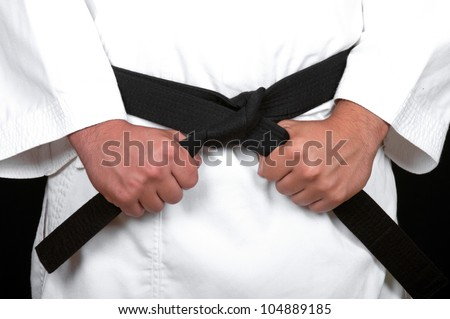 karate man tying the knot to his black belt on black background - stock photo