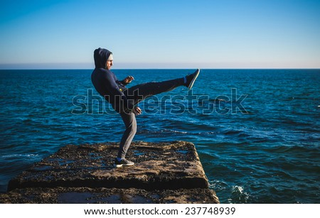 karate training on the shores of the  sea - stock photo